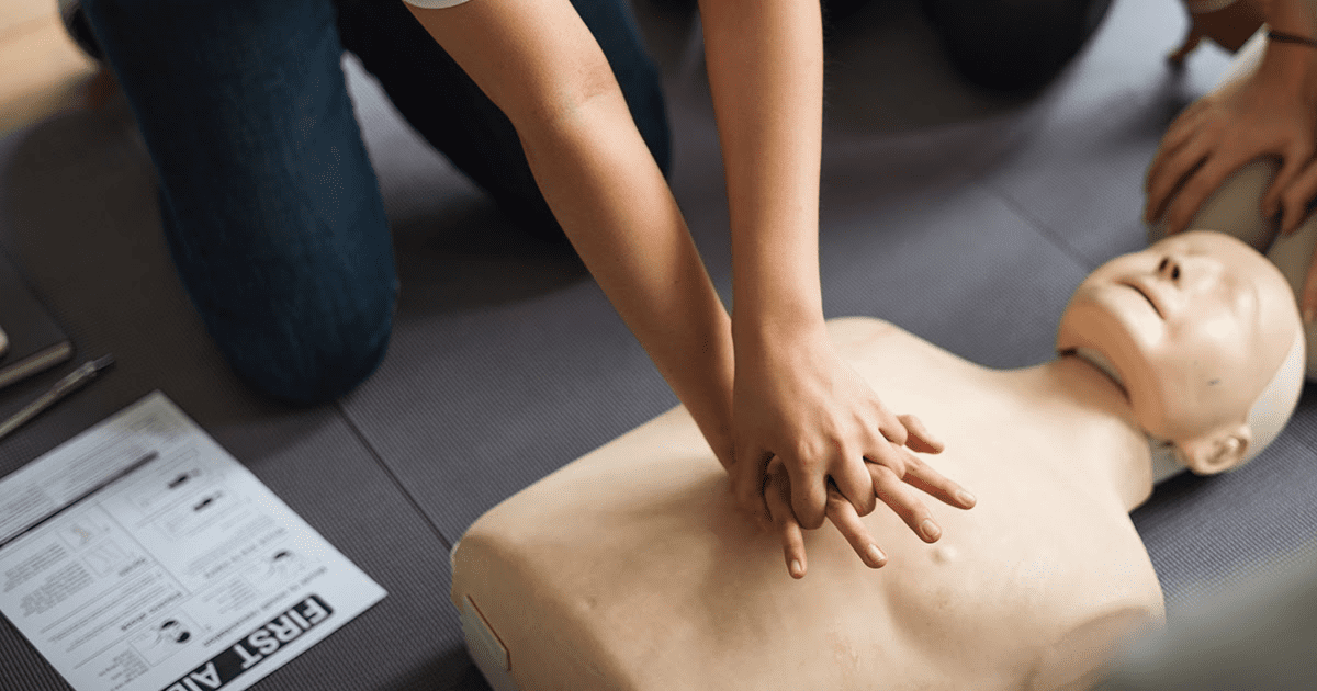Person performing CPR on a first aid dummy